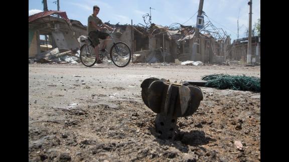 A man rides a bike past the tail of a bombshell outside Slovyansk, Ukraine, on July 10.