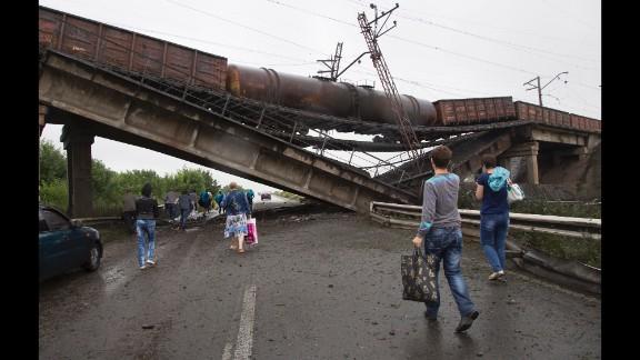 People walk under a destroyed railroad bridge near the village of Novobakhmutivka on Monday, July 7.