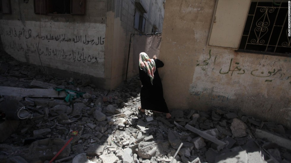 "A Palestinian woman carries belongings from her family's house, which police said was destroyed in an Israeli airstrike in Gaza City on Wednesday, July 9. In response to continuing rocket attacks from Hamas and other militants in Gaza, Israel has begun <a href=""http://www.cnn.com/2014/07/10/world/meast/mideast-tensions/index.html"">its own wave of aerial bombardment.</a> Israeli Prime Minister Benjamin Netanyahu said the offensive would continue ""until the firing at our communities stops and quiet is restored."""