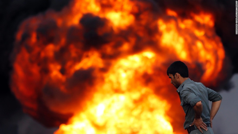 "An Afghan policeman looks at a fire after <a href=""http://www.cnn.com/2014/07/05/world/asia/afghanistan-truck-fires/index.html"">an overnight attack by the Taliban</a> on Saturday, July 5. More than 400 trucks carrying fuel and oil were burning on roads west of Kabul, Afghanistan, police spokesman Hashmatullah Stanekzai said. The Taliban claimed in a statement that their fighters had attacked a parking depot used by trucks delivering supplies to NATO."