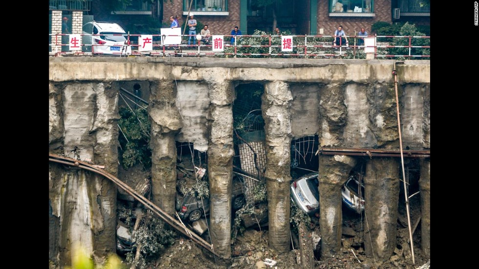 Cars are seen in a sunken parking lot after heavy rainfall hit Chengdu, China, on Wednesday, July 9. When the ground gave way, four cars fell into the pit and one was left stuck on the edge of a railing, according to local media.