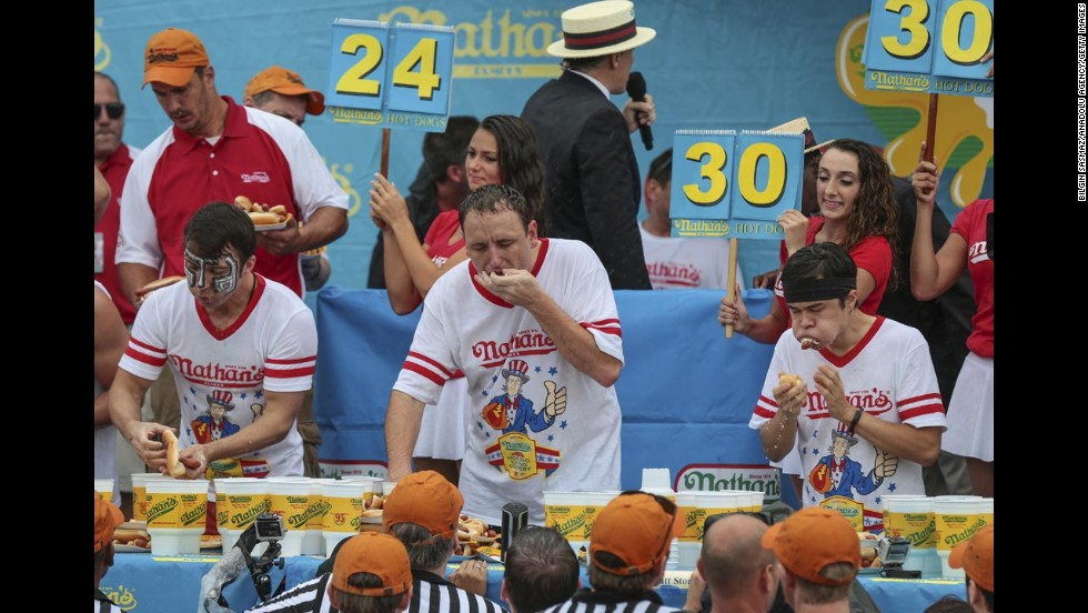"From left, competitive eaters Tim Janus, Joey Chestnut and Matt Stonie wolf down hot dogs Friday, July 4, during the 98th annual <a href=""http://www.cnn.com/2014/07/04/us/gallery/coney-hot-dog/index.html"">Nathan's Famous Hot Dog Eating Contest</a> at Coney Island in New York. Chestnut ate 61 hot dogs to win the men's competition for the eighth straight year."