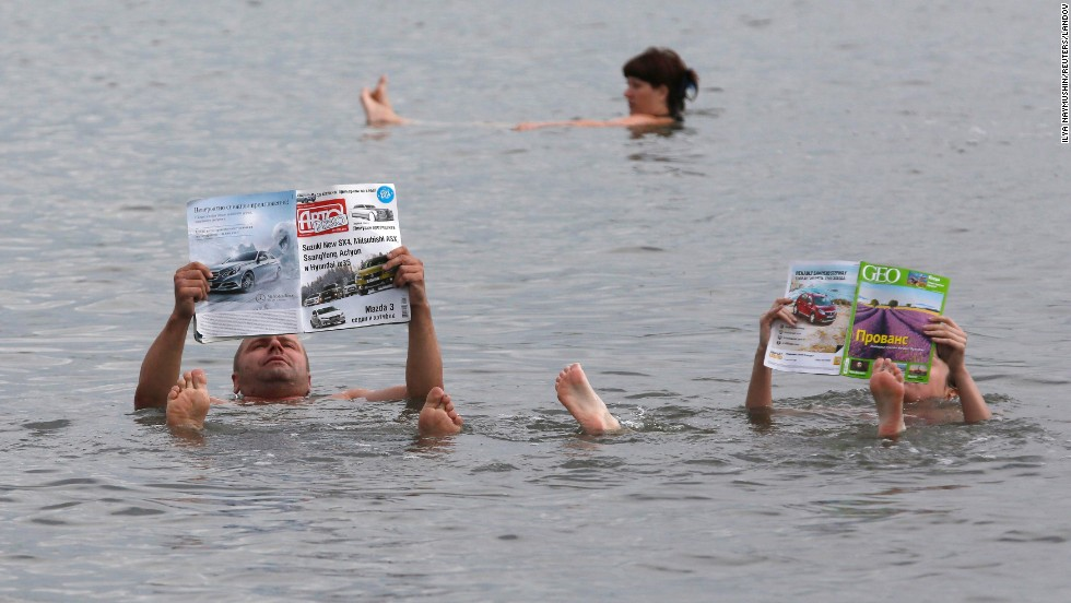 A couple reads magazines as they float in the salt waters of Lake Tus in Russia's Khakassia region, southwest of the Siberian city of Krasnoyarsk, on Saturday, July 5. During the summer, many Russians travel to the lake, famous for the curative properties of its black and blue sediments, to bathe in the salty water and smear themselves with mud.