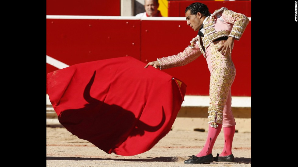 The shadow of a bull falls on the cape of bullfighter Ivan Fandino on Wednesday, July 9. Each day's run ends in the bull ring.