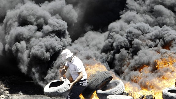 A Palestinian burns tires during clashes with Israeli security forces following a protest near the northern city of Nablus, in the occupied West Bank on July 11, 2014.