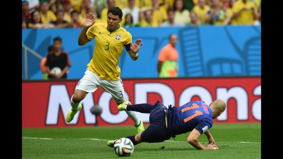 Brazil defender and captain Thiago Silva, left, reacts after fouling Netherlands forward Arjen Robben.