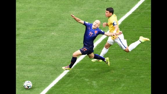 Brazil defender and captain Thiago Silva, right, fouls Netherlands forward Arjen Robben.