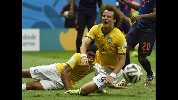 Brazil defender David Luiz, center, falls after a tackle.