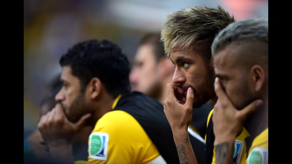 Brazil's injured player Neymar, right, is seen on the bench during the game.
