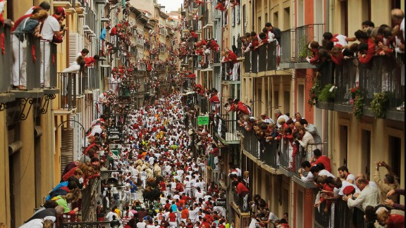 People watch as revelers and bulls fill a street on July 12.