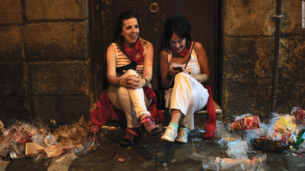 Two women sit on the street during the San Fermin festival on July 12.