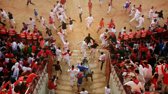Revelers and bulls run as they enter the bullring on July 13.