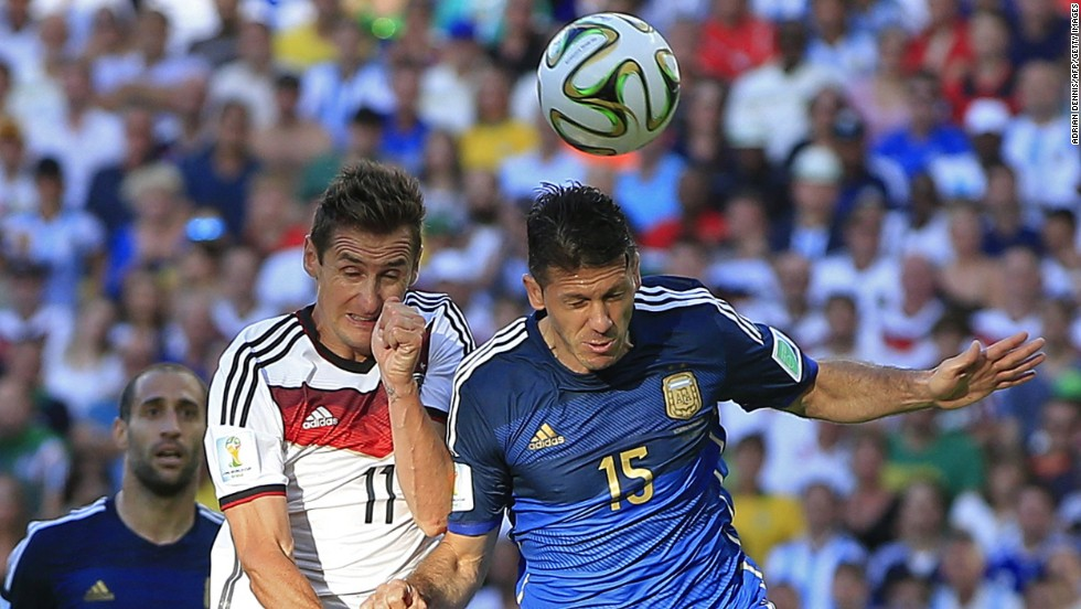 Klose, left, goes up for a header with Argentine defender Martin Demichelis.