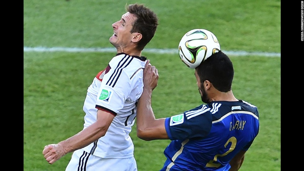 German forward Miroslav Klose, left, and Argentine defender Ezequiel Garay compete for the ball.