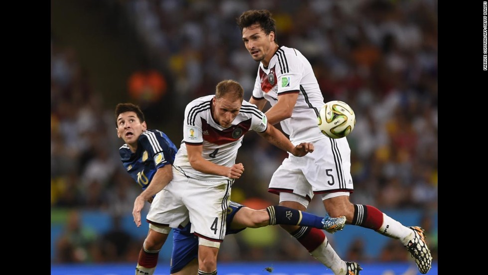 German defender Benedikt Howedes heads the ball away near Messi, left, and teammate Mats Hummels.