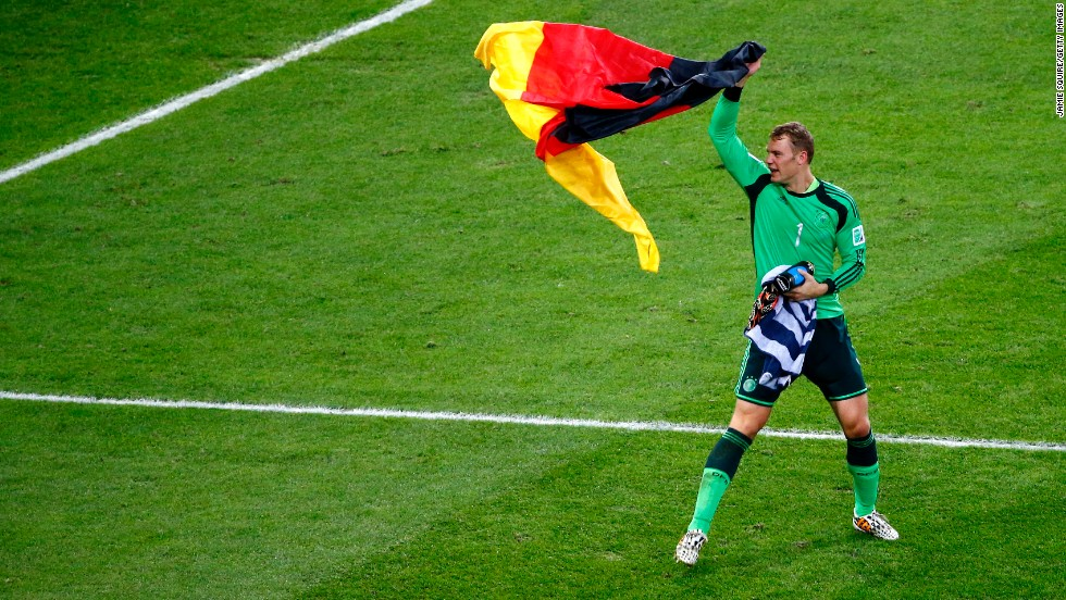 Goalkeeper Manuel Neuer celebrates with a German flag after the match.