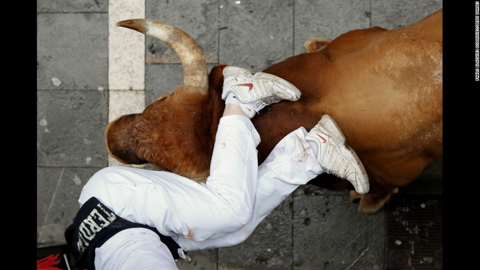 A bull horns a runner in Pamplona, Spain, on the last day of the San Fermin festival's annual running of the bulls Monday, July 14. The bull run, a 400-year tradition, takes place over eight days.