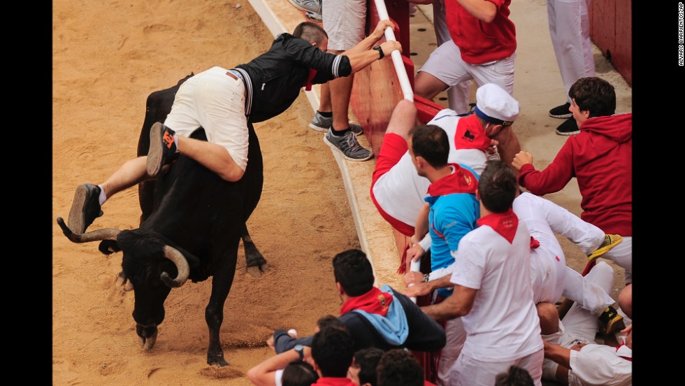 A man tries to protect himself July 14 in the bull ring where each bull run ends.