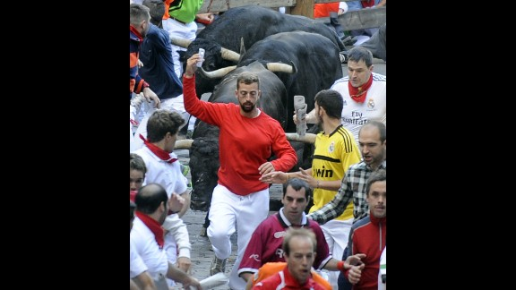 A man takes a selfie as he runs in front of bulls on Friday, July 11.