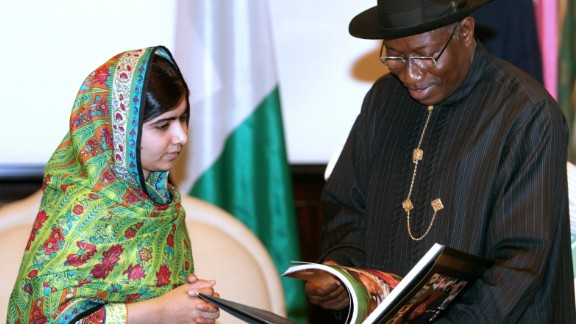 Pakistani education activist Malala Yousafzai (L) watches on July 14, 2014 Nigerian President Goodluck Jonathan look at a book at the State House in Abuja. Malala on July 14 urged Jonathan to meet with parents of the schoolgirls kidnapped three months ago by Boko Haram. Malala, who survived a Taliban assassination attempt in 2012 and has become a champion for access to schooling, was in Abuja on her 17th birthday to mark the somber anniversary of Boko Haram's April 14 abduction of 276 girls from a secondary school in the northeast Nigerian city of Chibok.  AFP PHOTO / WOLE EMMANUELWOLE EMMANUEL/AFP/Getty Images