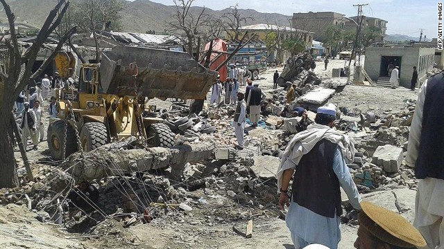 Afghans remove debris after a suicide attack at a market in Afghanistan's Paktika province in July 2014.