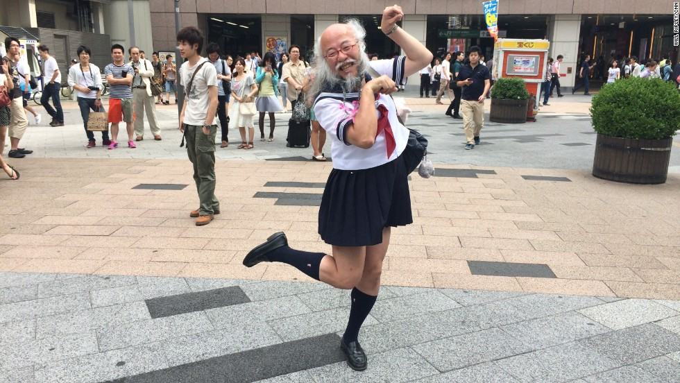 "Hideaki Kobayashi, 51, strikes his signature ""cat"" pose outside Akihabara station in Tokyo on Sunday July 13.  Underneath the Japanese schoolgirl facade, he is a patent-holding computer engineer and accomplished photographer."
