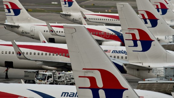 Airport groundstaff walk past Malaysia Airlines planes parked on the tarmac at the Kuala Lumpur International Airport in Sepang on June 17, 2014. Malaysia's government pledged on June 16 it 'will not rest' until missing flight MH370 is found but relatives said on the 100th day since the plane's disappearance that they wanted answers, not more promises.   AFP PHOTO/ Manan VATSYAYANA        (Photo credit should read MANAN VATSYAYANA/AFP/Getty Images)