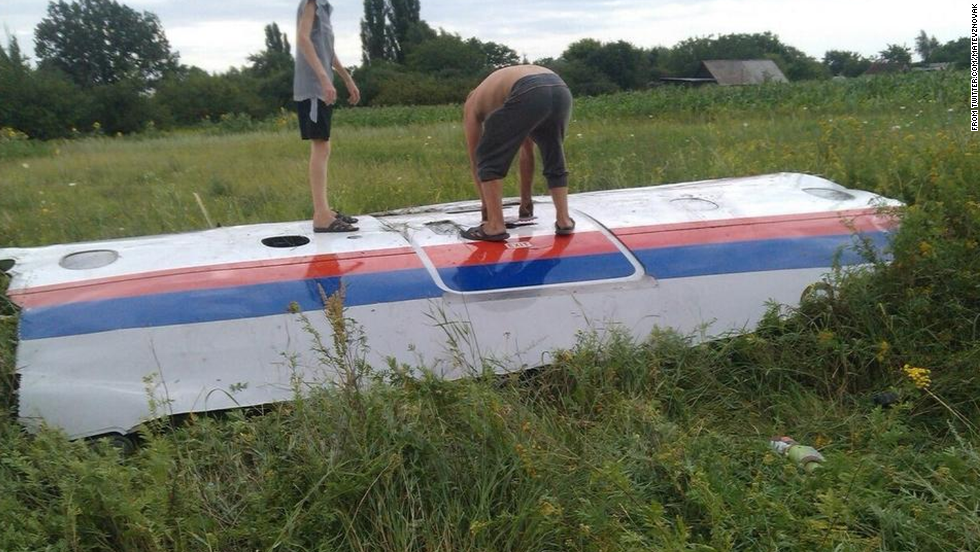 People inspect a piece of wreckage believed to be from Malaysia Airlines Flight 17. This image was posted to Twitter.
