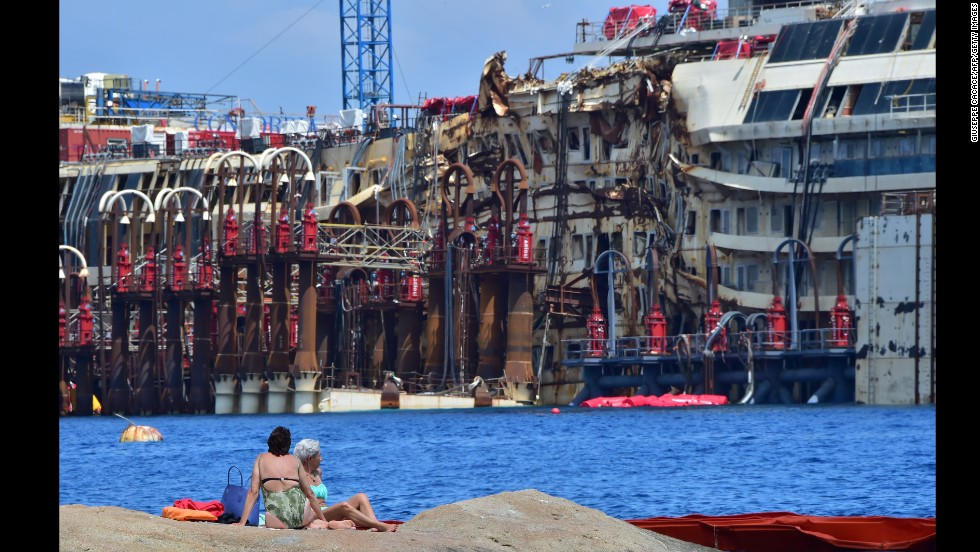 "People sunbathe on rocks facing the wrecked <a href=""http://www.cnn.com/2013/07/18/europe/gallery/costa-concordia/index.html"" target=""_blank"">Costa Concordia</a> cruise ship on Sunday, July 13, off the shore of Giglio, Italy. Two and a half years after it ran aground, crews began to raise the ship from the seabed on July 14."