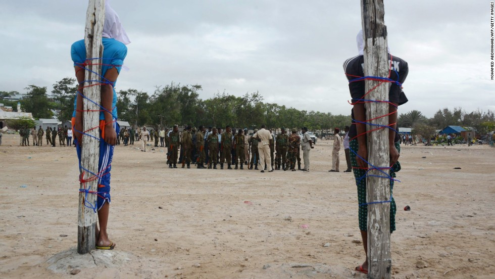 Two Somalis tied to large wooden stakes wait to be executed by a firing squad on Tuesday, July 15, in Mogadishu. They were convicted of murdering a Somali nurse working with a Turkish medical unit.