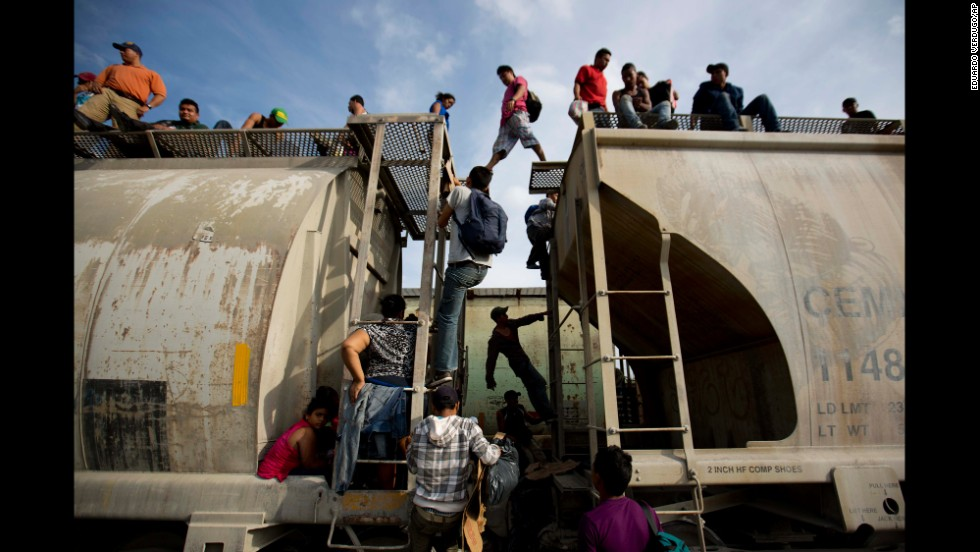 Central American migrants climb on a northbound train in Ixtepec, Mexico, during their journey toward the U.S.-Mexico border on Saturday, July 12.