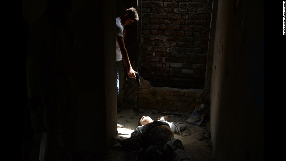 "A member of the Afghan intelligence force points his pistol toward the body of an alleged insurgent after <a href=""http://www.cnn.com/2014/07/16/world/asia/afghanistan-violence/index.html"" target=""_blank"">an attack by the Taliban </a>at Kabul's airport on Thursday, July 17."