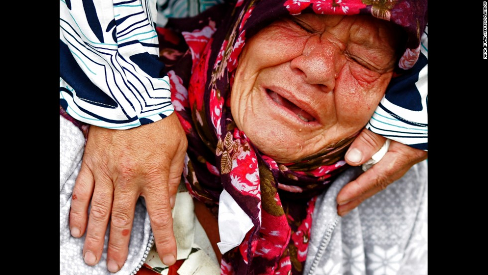 A Bosnian Muslim woman mourns while visiting the coffin of a relative at the Potocari Memorial Centre near Srebrenica on Friday, July 11. Bosnian Serb forces massacred nearly 8,000 Muslim men and boys in 1995. The remains of 175 newly identified bodies were found in dozens of mass graves.