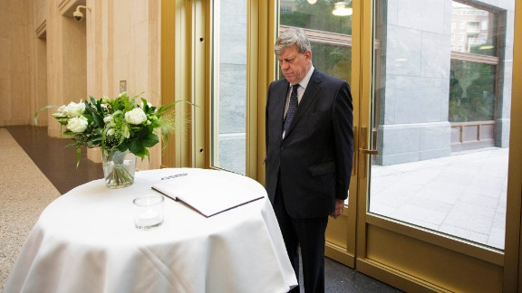 Dutch Justice Minister Ivo Opstelten observes a moment of silence after signing a condolence book in The Hague on July 18.