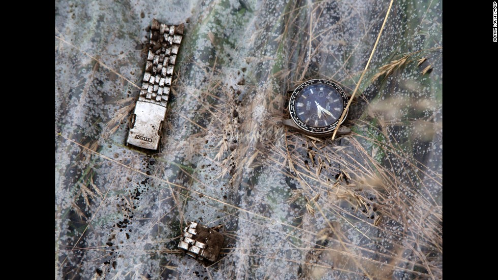 Pieces of a wristwatch lie on a plastic cover at the crash site.