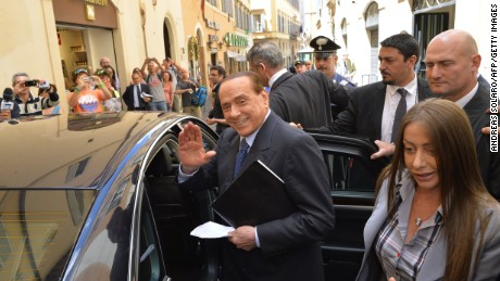 Caption:Italian former Prime Minister Silvio Berlusconi waves as he leaves after a press conference on June 18, 2014, in Rome. (Photo credit: ANDREAS SOLARO/AFP/Getty Images)