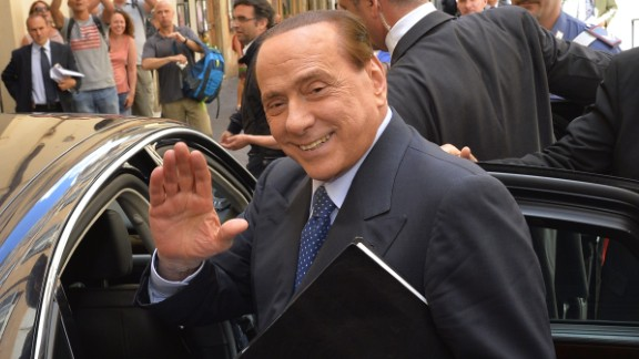Italian former Prime Minister Silvio Berlusconi waves as he leaves a press conference on June 18, 2014, in Rome.