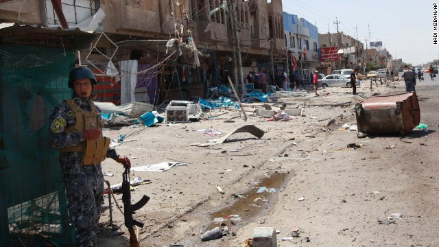 An Iraqi policeman and civilians inspect the site of a bomb attack in the Jihad district in Baghdad, Saturday, July 19.