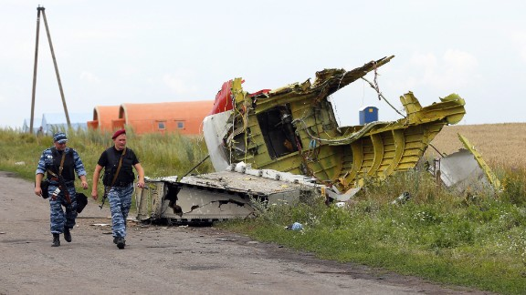 Armed rebels walk past large pieces of the Boeing 777 on July 19, 2014.