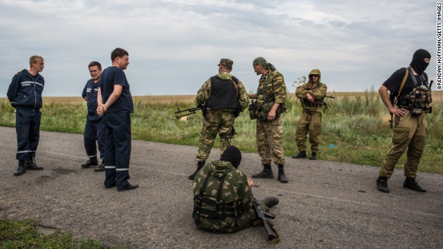 Pro-Russia separatist fighters and emergency personnel gather near the scene of the crash of Malaysia Airlines flight MH 17 on July 19, 2014 in Grabovo, Ukraine. Malaysia Airlines flight MH17 was travelling from Amsterdam to Kuala Lumpur when it crashed killing all 298 on board including 80 children. The aircraft was allegedly shot down by a missile and investigations continue over the perpetrators of the attack. (Photo by Brendan Hoffman/Getty Images