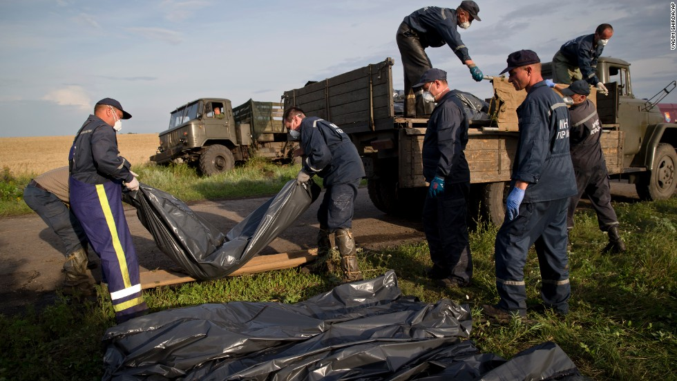 Workers load bodies of victims onto a truck at the crash site on July 19.