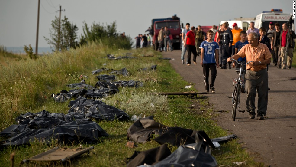 Victims' bodies are placed by the side of the road on July 19, 2014, as recovery efforts continue at the crash site. International officials lament the lack of a secured perimeter.
