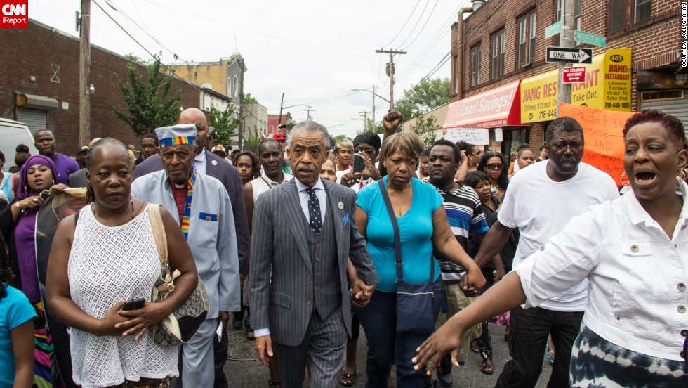 "People participate in a demonstration against the death of Eric Garner after he was taken into police custody in Staten Island.<a href=""http://ireport.cnn.com/docs/DOC-1153998""> Joel Graham</a> photographed the July 2014 demonstration, and captured this image of Garner's friends and family rallying alongside the Rev. Al Sharpton."