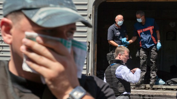 A man covers his face with a rag as members of the Organization for Security and Co-operation in Europe and the Dutch National Forensic Investigations Team inspect bodies in a refrigerated train near the crash site in eastern Ukraine on July 21, 2014.