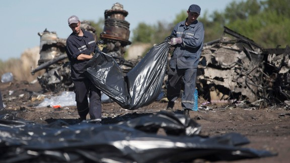 Emergency workers carry a victim's body in a bag at the crash site on July 21, 2014.