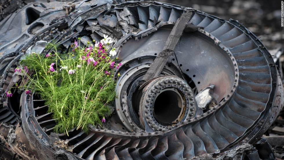 Wildflowers lie on an engine from the crashed jet on Saturday, July 19.