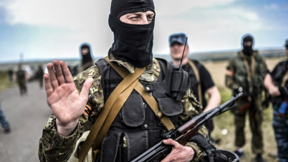 An armed pro-Russian separatists gestures as he blocks the way to the crash site of Malaysia Airlines Flight MH17, near the village of Grabove, in the region of Donetsk on July 20, 2014.