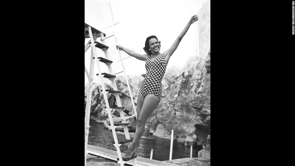 Actress Dorothy Dandridge showcases her trademark Hollywood glamor while frolicking in a checkered one-piece in 1957.