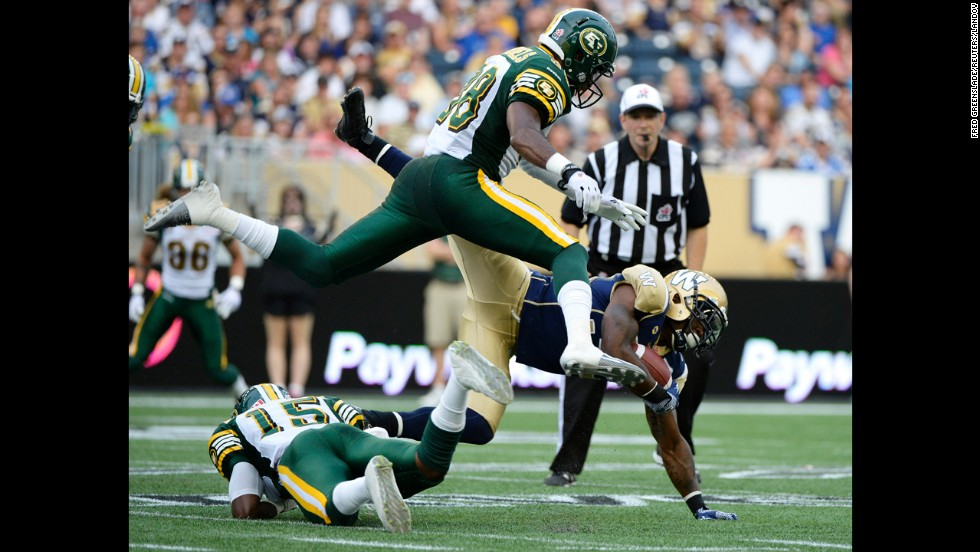 Nic Grigsby of the Winnipeg Blue Bombers is tackled by Edmonton's Chris Rwabukamba, left, and Eric Samuels during a CFL football game Thursday, July 17, in Winnipeg, Manitoba.