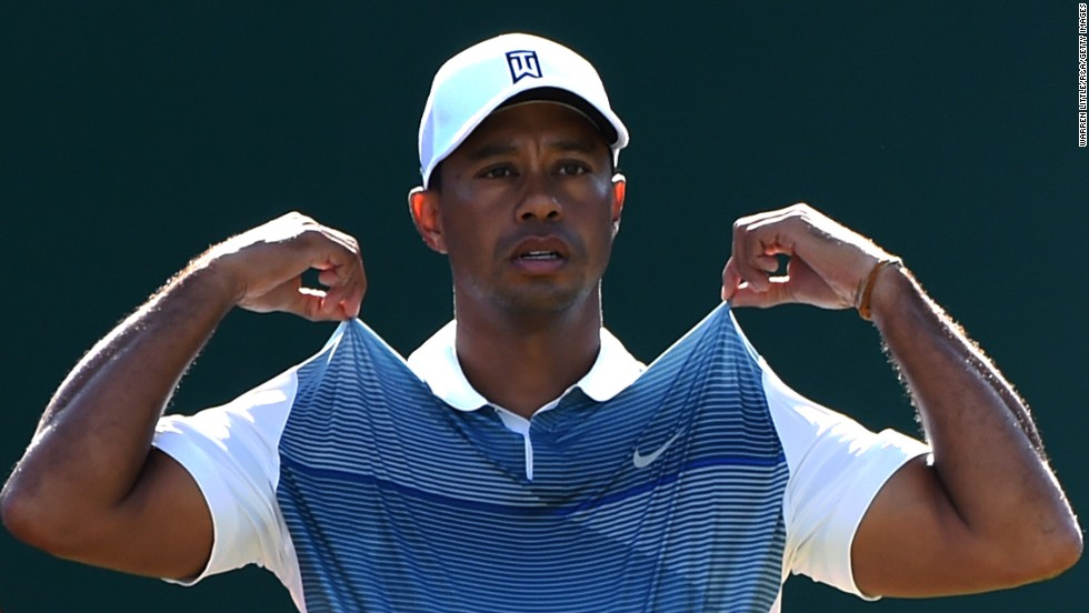 Tiger Woods adjusts his shirt before teeing off Thursday, July 17, at the British Open in Hoylake, England. Woods finished the tournament in 69th place, 23 strokes behind winner Rory McIlroy.